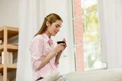 Young female sitting next to window, thinking holding wineglass with both hands. Royalty Free Stock Photography