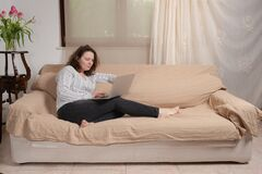 Free Young Female Sitting On The Couch In The Living Room And Working Remotely At Home Royalty Free Stock Photo - 185706895
