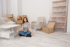 Young female sitting in relaxation pose on the floor after relocation to new home. Stock Photos