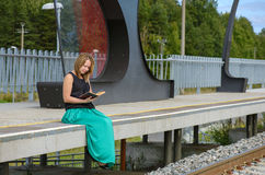 Young female sitting on the station and reading Royalty Free Stock Photo