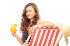 Young female sitting on a sun lounger and drinking a cocktail Royalty Free Stock Photo