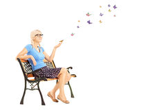 Young female sitting on a wooden bench and looking at butterflies Royalty Free Stock Images