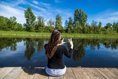 Young female sitting on wooden dock and taking pictures with mobile phone stock photography