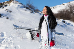 Young female skier basking in sunlight. Beautiful young woman with long dark hair and eyes closed standing with skis and helmet as she takes in the sun on Royalty Free Stock Photography