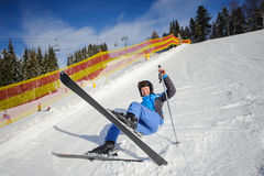 Young female skier after the fall on mountain slope Royalty Free Stock Image