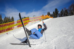 Young female skier after the fall on mountain slope Stock Photos