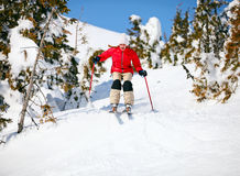 Young female skier jumping on snowy slope Stock Photo