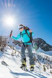 Young female skier. Woman ascending a snowy slope Royalty Free Stock Photos