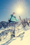 Young female skier. Woman ascending a snowy slope Royalty Free Stock Image