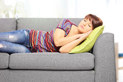 Young female sleeping on sofa at home Royalty Free Stock Photos