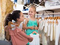 Young female with small girl in kids apparel boutique. Young female with small girl choosing pink dress in kids apparel boutique Stock Photos