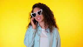 Young female smiling and talking on mobile phone over yellow background. Beautiful mixed race girl holding and using stock footage