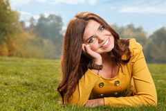 Young female smiling. Young female in yellow dress lying down on grass smiling looking at camera Stock Photos