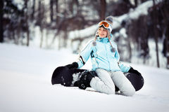 Young female snowboarder sitting Royalty Free Stock Photos