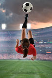Young Female Soccer Player. Kicking the ball in mid-air inside stadium stock images