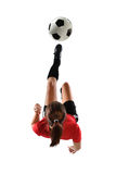 Young Female Soccer Player. Kicking the ball in mid-air isolated over white background stock images