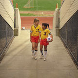 Young female soccer players at stadium field. Two soccer players walking off field Stock Photo