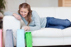 Young female on the sofa looking into her shopping bags Royalty Free Stock Image
