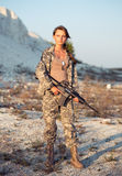 Young female soldier dressed in a camouflage with a gun in the l Stock Photo