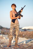 Young female soldier dressed in a camouflage with a gun in the l Royalty Free Stock Images