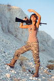 Young female soldier dressed in a camouflage with a gun in the l Royalty Free Stock Photos