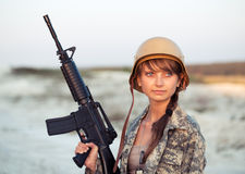 Young female soldier dressed in a camouflage with a gun in the o. Young beautiful female soldier dressed in a camouflage with a gun in the outdoor Stock Photography