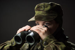 Young female soldier observe with binoculars. War, military, army people concept Stock Photos