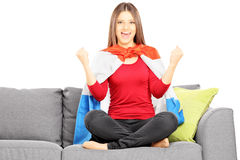 Young female sport supporter sitting on a modern couch and cheer Royalty Free Stock Photography