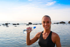 Young female in sports attire rests with water Royalty Free Stock Photo