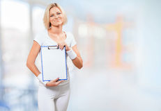 A young female in sports clothing holding clipboard Royalty Free Stock Photos