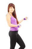 Young female in sportswear exercising with dumbbells Royalty Free Stock Photo
