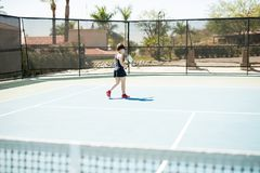Tennis player going for a serve. Young female in sportswear walking toward the base line on tennis court with ball and racket Stock Image