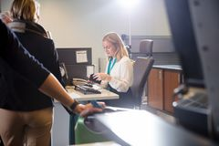 Staff Examining Boarding Pass Of Passenger At Airport Stock Photos
