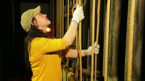 A young female stage worker in gloves removes the mount from a cable lifting mechanism of a theater curtain and lifts it