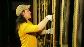 A young female stage worker in gloves removes the mount from a cable lifting mechanism of a theater curtain. The average plan stock footage
