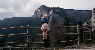 Young female standing on the edge of the cliff and raising her hands up against high rocky mountains . Happy girl stock video