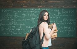 Young female standing in the middle of classroom with huge pile of books in her hand. Beautiful brunette student royalty free stock photos