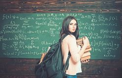 Young female standing in the middle of classroom with huge pile of books in her hand. Beautiful brunette student stock photo