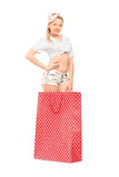 A young female standing into a red spotted shopping bag Stock Image