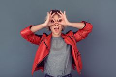 Young woman standing in leather jacket on grey wall grimase playful royalty free stock photos
