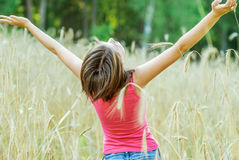Young female stands in crop field Royalty Free Stock Photos