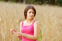 Young female stands in crop field holding flower Stock Image