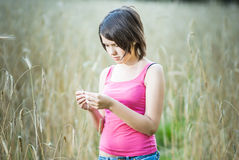 Young female stands in crop field holding flower Royalty Free Stock Images