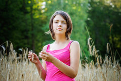 Young female stands in crop field holding flower Stock Photos