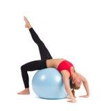 Young Female Stretching on Exercise Ball. With one leg raised. Full length studio shot on white background royalty free stock photo