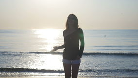 Young female stretching on the shore of the beach at sunset stock footage
