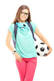 Young female student with backpack holding a soccer ball Royalty Free Stock Images