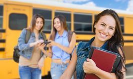 Young Female Student with Books Near School Bus. Young Teenaged Female Students with Books Near a School Bus royalty free stock photos