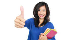 Young female student with books showing thumb up. Portrait of Young female student with books showing thumb up isolated over white background Stock Photography