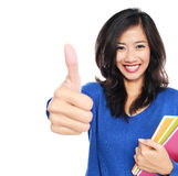 Young female student with books showing thumb up Royalty Free Stock Image